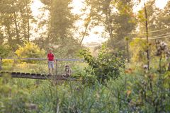 UKRAINE, Voronizh - September 2, 2018: Two children play on a wooden bridge over the river on a sunny day stock photography