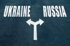 UKRAINE vs RUSSIA  choice concept. Two direction arrows on asphalt Royalty Free Stock Images