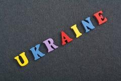 UKRAINE-Wort auf dem schwarzen Bretthintergrund verfasst von den hölzernen Buchstaben des bunten ABC-Alphabetblockes, Kopienraum  Lizenzfreies Stockbild