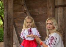 Ukrainean moder och hennes dotter nära gammalt hus Royaltyfri Foto