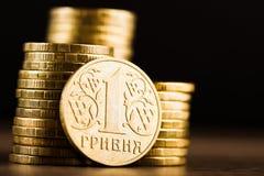 Ukrainer einer hryvnia Münze und Goldgeld auf dem Schreibtisch Stockfotos
