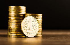 Ukrainer einer hryvnia Münze und Goldgeld auf dem Schreibtisch Stockbilder