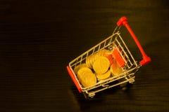 Ukrainer Hryvnia-Münzen in der Einkaufslaufkatze schwarzes backgroun Stockbild