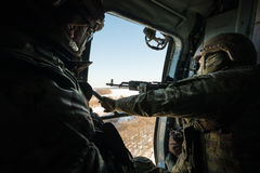 Ukrainian army helicopter patrols the area of of the antiterrori. DONETSK REGION, UKRAINE - Dec 05, 2016: Soldiers of Armed Forces of Ukraine with guns on board Stock Photos