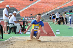 Ukrainian athlete landed in the sand Royalty Free Stock Image