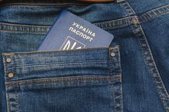 Ukrainian biometric passport in the back pocket of dark blue trousers. royalty free stock photography