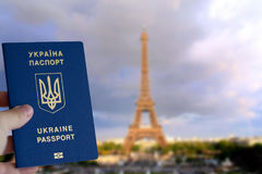 Ukrainian biometric passport. Of a new sample against a background of a blurred background with the Eiffel Tower. Cancellation of visas to Paris Royalty Free Stock Photo