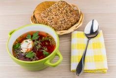 Ukrainian borsch, bread in basket, spoon on napkin on table Royalty Free Stock Photos