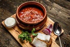 Ukrainian borsch soup and garlic buns on the table. With bread and bacon stock photo