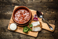 Ukrainian borsch soup and garlic buns on the table. With bread and bacon royalty free stock photography