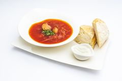 Ukrainian borscht with beef, green, bread and sour cream in whit royalty free stock image