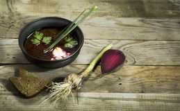 Ukrainian borscht with beet, garlic and a spoon. On a wooden background stock photography