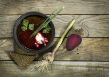 Ukrainian borscht with beet, garlic and a spoon. On a wooden background stock image
