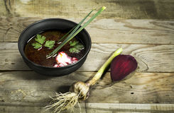 Ukrainian borscht with beet, garlic and a spoon. On a wooden background stock photo