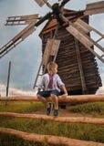 Ukrainian boy near old mill. Little ukrainian boy is sitting on the hedge near old wooden mill stock photo