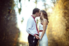 Ukrainian brides in traditional costumes embroidered shirts outdoors. Embrace and kiss stock image