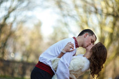 Ukrainian brides in traditional costumes embroidered shirts outdoors. Embrace and kiss stock photography