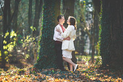 Ukrainian brides in traditional costumes embroidered shirts outdoors. Embrace tree wood stock photo
