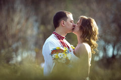 Ukrainian brides in traditional costumes embroidered shirts outdoors. Kiss royalty free stock photography