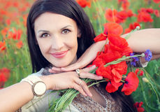 Ukrainian brunette woman with a bouquet of poppies Stock Image