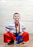 Ukrainian child performing a traditional dance. Ukrainian talented child performing a traditional dance move with a leap in mid air while wearing folk costume Stock Images
