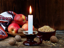 Ukrainian Christmas concept for greeting card. Composition of burning candle, apples, walnuts, wheat on wooden background. Copy sp Stock Image