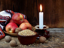 Ukrainian Christmas concept for greeting card. Composition of burning candle, apples, walnuts, wheat on wooden background. Copy sp Royalty Free Stock Photos