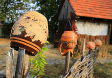 Ukrainian clay jugs on wooden fence Stock Images