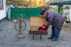 Ukrainian country man examines an ancient wooden trunk Stock Photo