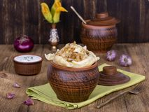 Ukrainian dishes - vareniki or dumplings with mashed potatoes or cottage cheese in clay pot on a wooden background. Close up Stock Photo
