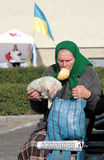 Ukrainian elector. LUTSK, UKRAINE - 15 OCTOBER 2014: An unidentified elderly woman with a piece of bread in your mouth sitting at outdoor pending meeting on stock images
