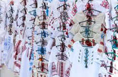 Ukrainian embroidered shirts, national handmade clothes. Traditional linen shirt with embroidered flowers and ornaments at local. Market at state fair.  Fair royalty free stock images