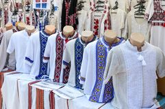 Ukrainian embroidered shirts, national handmade clothes. Traditional linen shirt with embroidered flowers and ornaments at local. Market at state fair.  Fair royalty free stock photo