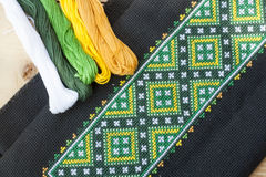 Ukrainian embroidery on the black fabric and thread embroidery on a light wooden table Stock Photo