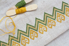 Ukrainian embroidery on the linen fabric and thread embroidery on a wooden table Royalty Free Stock Photos