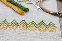 Ukrainian embroidery on the linen fabric and thread embroidery on a wooden table Stock Image