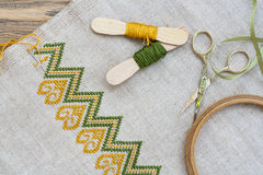 Ukrainian embroidery on the linen fabric and thread embroidery on a wooden table Stock Photos
