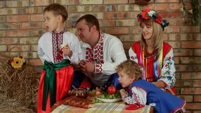 Ukrainian Family Dinner. A large family dressed in traditional costume resting at the farm stock footage
