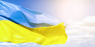 Ukrainian flag against a blue cloudy sky. Flag of Ukraine in sunlight and glare. Blue and yellow flag develops Royalty Free Stock Image