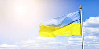 Ukrainian flag against a blue cloudy sky. Flag of Ukraine in sunlight and glare. Blue and yellow flag develops Stock Image