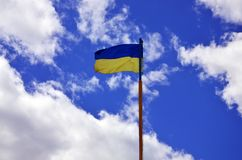 Ukrainian flag against the blue sky with clouds. The official flag of the Ukrainian state includes yellow and blue color. S Stock Photo