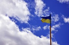 Ukrainian flag against the blue sky with clouds. The official flag of the Ukrainian state includes yellow and blue color. S Royalty Free Stock Images