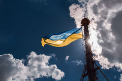 Ukrainian flag on the background of blue sky with clouds. Flag of Ukraine backlit fluttering in the wind Royalty Free Stock Photography