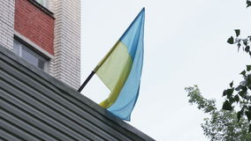 Ukrainian flag in city. On roof building hangs Ukrainian flag stock footage