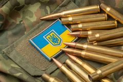 Ukrainian flag and coat of arms against camouflage and battle bu. Llets. The concept of the Ukrainian defense army, highlight stock photography