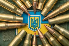 Ukrainian flag and coat of arms against camouflage and battle bullets. The concept of the Ukrainian defense army, highlight. Ukrainian flag and coat arms against stock image