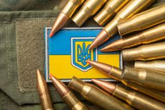 Ukrainian flag and coat of arms against camouflage and battle bullets. The concept of the Ukrainian defense army, highlight. Ukrainian flag and coat of arms stock images