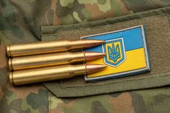 Ukrainian flag and coat of arms against camouflage and battle bullets. The concept of the Ukrainian defense army, highlight. Ukrainian flag and coat arms against royalty free stock photography