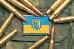 Ukrainian flag and coat of arms against camouflage and battle bullets. The concept of the Ukrainian defense army, highlight. Ukrainian flag and coat of arms stock photos