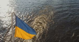 Ukrainian flag on a background of waves. The Ukrainian flag flies freely against the waves from the boat stock video footage